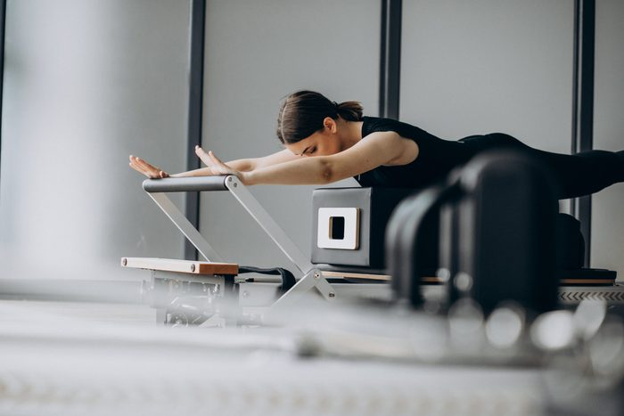 pilates reformer   woman using a pilates reformer at the gym