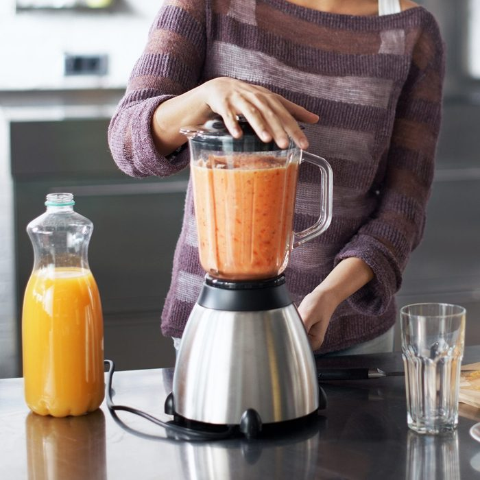how to make frozen drinks A woman smiling happily while preparing a smoothie in her kitchen at home