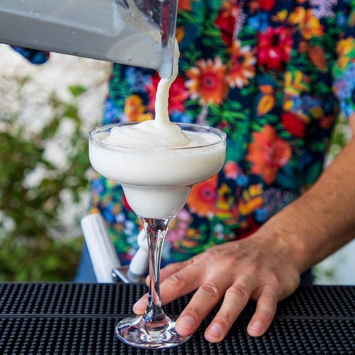 how to make frozen drinks Pouring White Smoothie Into Cocktail Glass