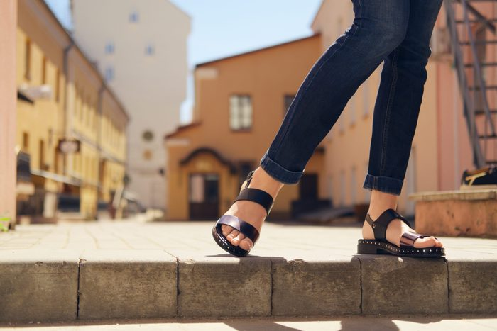 womens sandals canada | someone wearing comfortable sandals standing on a ledge