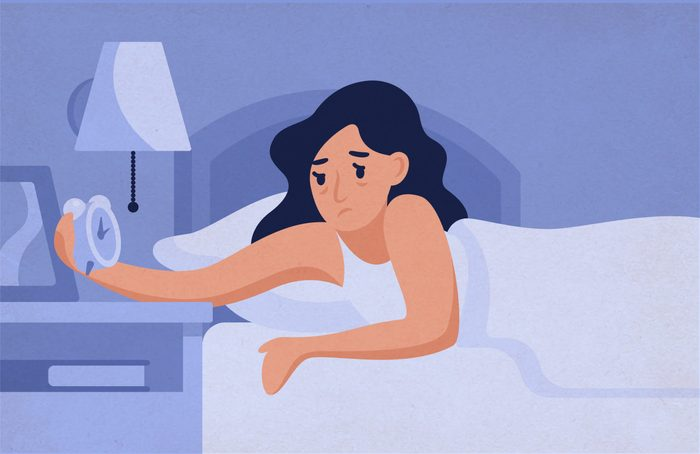 Sleepy,woman,lying,on,bed,and,looking,at,alarm,clock