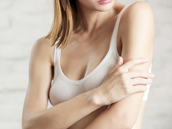 Photo,of,a,young,attractive,woman,touching,her,arm,,dry