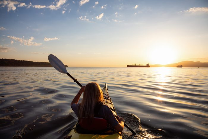 aquafit   woman paddling a canoe on a lake