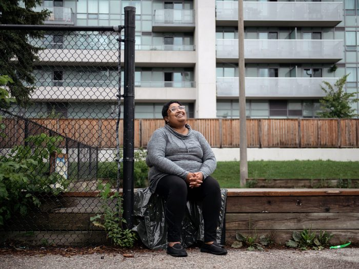 workplace-accommodations | writer krystal jagoo sitting in front of an apartment building