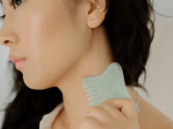 gua sha tools in Canada | image of someone using a jade comb gua sha tool on their neck