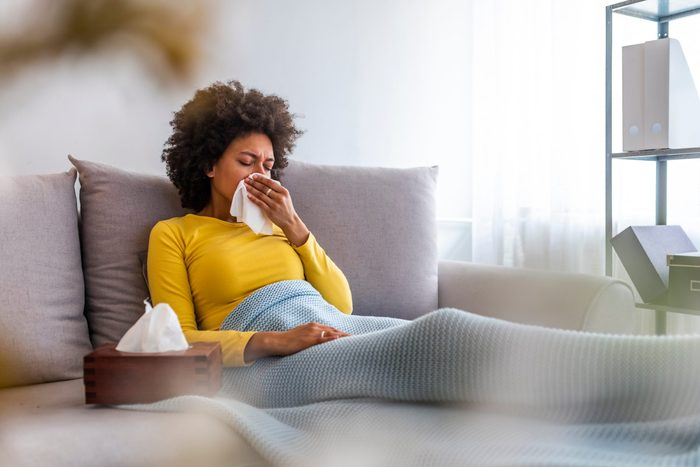 flu season 2021   woman blowing her nose into a tissue